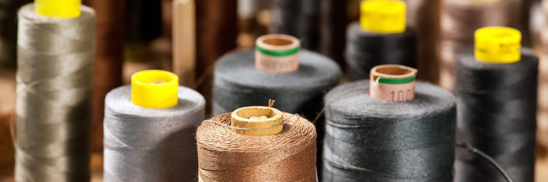 Various colored yarns on bobbins at a tailor 1500_500
